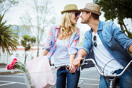 Hip young couple on a bike ride on a sunny day in the city