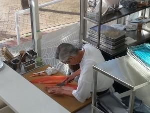 Master Sushi Chef Yoshi Tabo slicing salmon for sushi