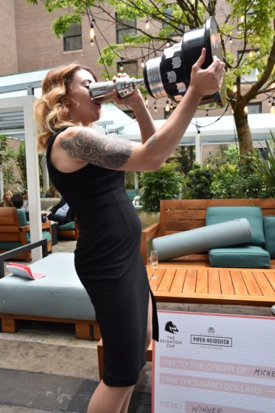 Michelle Medwin takes the traditional drink from the Deighton Cup's Cocktail Jockey trophy - photo by Cathy Browne